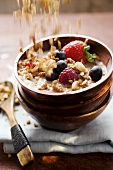 Cereal flakes falling onto berry muesli in cereal bowl