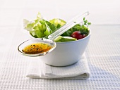 Spoonful of salad dressing lying on a bowl of salad