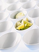 Lots of white bowls, two full of lime pieces