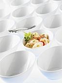 Kartoffelsalat in einer Schale zwischen leeren Schalen