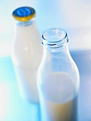 Two milk bottles, one opened