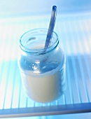 Opened yoghurt jar with spoon in fridge