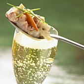 Shrimp cocktail on a spoon, served with a glass of champagne