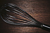 Whisk on wooden background