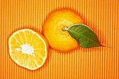 Whole and half mandarin orange on orange background