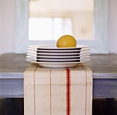 Pile of plates with a lemon