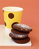 Chocolate biscuits and yellow beaker of milk