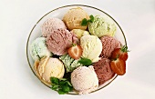 Bowl of different ice creams, strawberries and mint leaves
