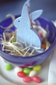 Blue felt bunny in a bowl of straw