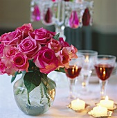 Pink roses, tea lights and glasses