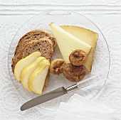 Cheese, dried figs, bread and pear on plate