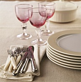 Cutlery, pile of plates and wine glasses
