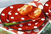 Halved tomato with knife on spotted plate