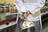 Chef with a domed food cover in his hand
