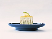 A piece of lemon ice cream cake on blue plate