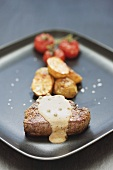 Peppered steak with baked potatoes and tomatoes