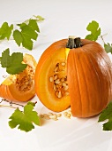 A pumpkin with a piece cut out and vine leaves