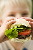 A little boy eating a burger with tomato and lettuce