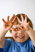 Kleiner Junge mit Schokoladen-Händen