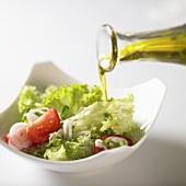 Olivenöl über Blattsalat mit Tomaten gießen