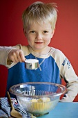 Small boy making a cake