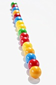 Lots of coloured chewing gum balls in a row