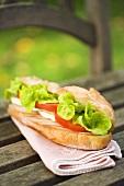 Ein Sandwich mit Hähnchenbrust, Käse, Tomate und Salat