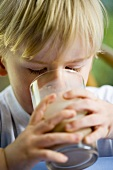 Small boy drinking a glass of cocoa