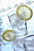 Three glasses of water with ice cubes and lemon