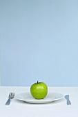 Ein Apfel auf einem Teller mit Besteck