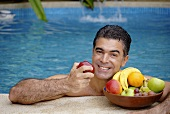 Man in pool with a bowl of fruit