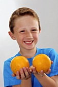 Small boy holding a grapefruit in each hand