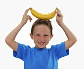 Small boy with a banana on his head