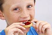 Boy biting into a jam tart