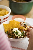 Chili con carne with sour cream and corn chips