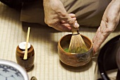 Tea master at tea ceremony, stirring tea with tea whisk