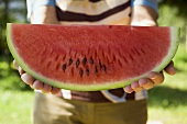 Model holding a slice of watermelon