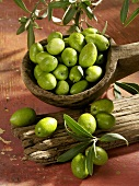 Fresh green olives in a wooden spoon