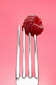 A raspberry speared on a fork