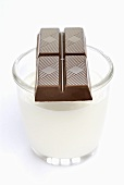 A piece of chocolate on a glass of milk