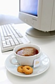 A cup of tea with biscuits in the saucer on a desk