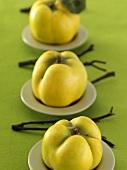 Three quinces on plates