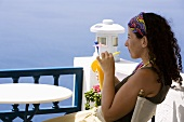 Woman drinking orange juice on a balcony