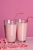 Two glasses of strawberry milk with straws