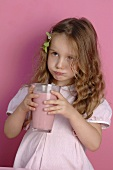 Small girl holding a glass of strawberry milk in her hands