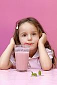 Small girl drinking strawberry milk through a straw