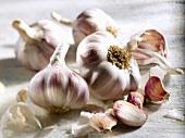 Four garlic bulbs and individual cloves of garlic
