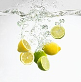 Lemons and lime halves falling into water