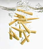 Baby corn cobs falling into water