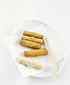 Raw and deep-fried spring rolls on a platter
